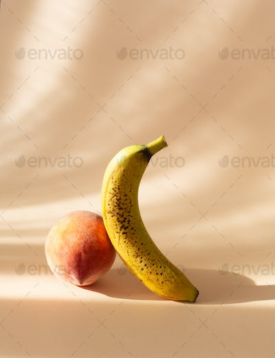Fresh peach and ugly banana on a pastel background with shadows