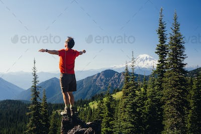 Male hiker standing with his arms outstretched on a mountain top, looking over the landscape.