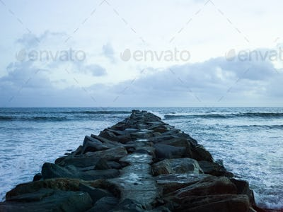View along a groyne built out of rocks onto the ocean.