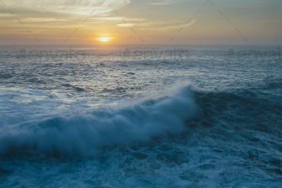 Sunset over crashing waves and surf. View out to the horizon.