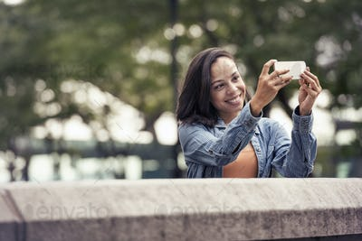 A woman taking a photograph or a selfie with a smart phone