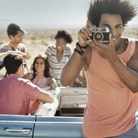 A group of friends by a convertible on a flat plain, one holding a camera.