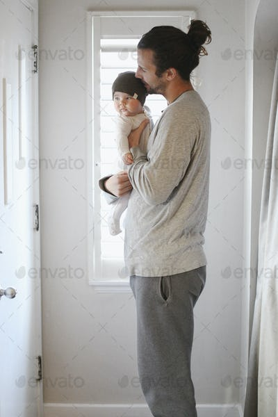 A father holding a young baby.
