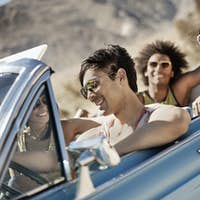 A group of friends in a pale blue convertible on the open road, surrounded by mountains.