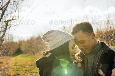 Two people, a couple walking in an orchard in winter.