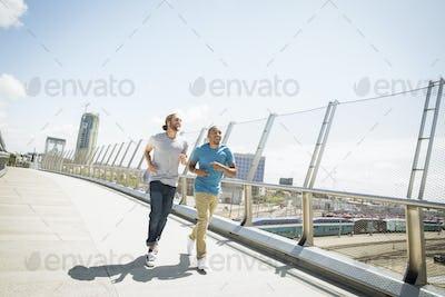 Two young men jogging along a bridge.