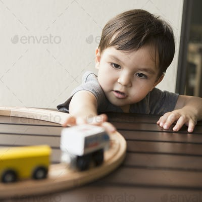 Young boy playing with a wooden train set.