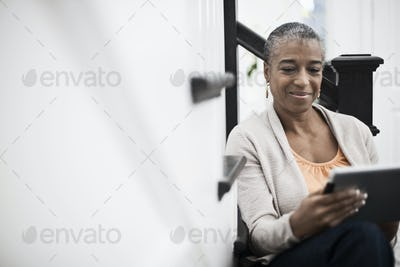 A mature woman seated in a hallway using a digital tablet.