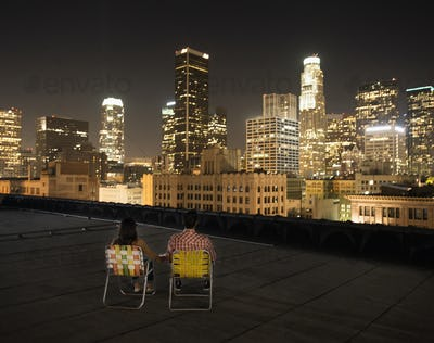A couple on a rooftop overlooking Los Angeles at night, sitting side by side looking over the city.