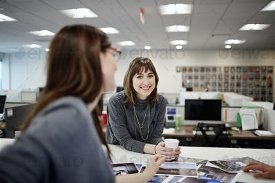 Two women seated in an office talking and laughing.