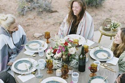 A small group of women enjoying an outdoor meal in a desert.