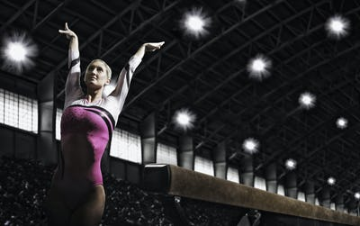 A young woman gymnast with her arms raised.