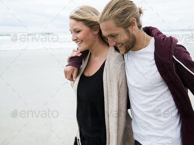 Young man and young woman walking on a beach, smiling.