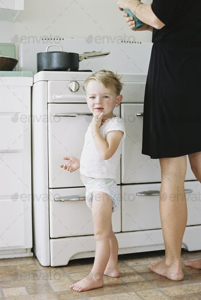 A woman and a child, a young boy standing barefoot in a kitchen.