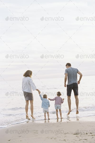 Couple playing with their son and daughter on a sandy beach by the ocean, holding hands.