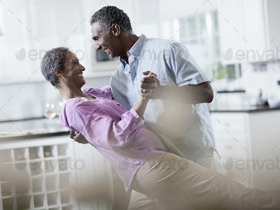 An affectionate mature African American couple, with their arms around each other dancing.