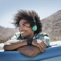 A young man with music headphones sitting in a pale blue convertible with mountains behind.