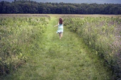 A girl running through a meadow in summer.