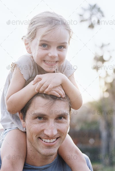 A man and his daughter smiling at the camera, the child sitting on his shoulders.