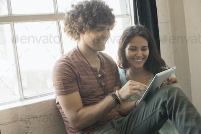 Loft living. A man and woman sitting by a window using a digital tablet.