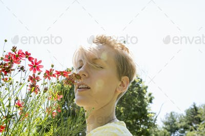 A young woman standing in a flower border, face to face with range rudbekia flowers.