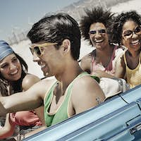 A group of friends in a pale blue convertible on the open road, driving across a flat plain.