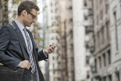 A working day. Businessman in a work suit and tie on a city street, using his phone.