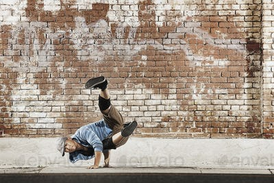 A young man doing a breakdance move balancing on his hands on the street of a city.