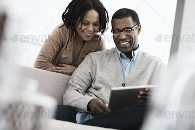 A couple, man and woman seated sharing a digital tablet.