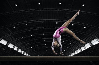 A young woman gymnast performing on the beam, balancing on her hands on a narrow piece of apparatus.