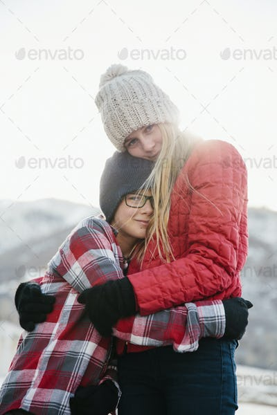 A brother and sister hugging each other.
