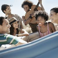 A group of friends in a blue convertible driving across a dry flat plain surrounded by mountains.