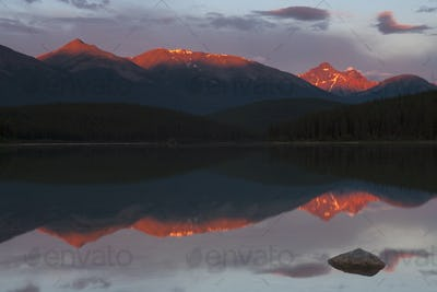 Mountains reflected in a lake and the sun reflecting off the snow covered high slopes.
