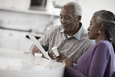 A grey haired couple sitting at a table, looking at information on a digital tablet.