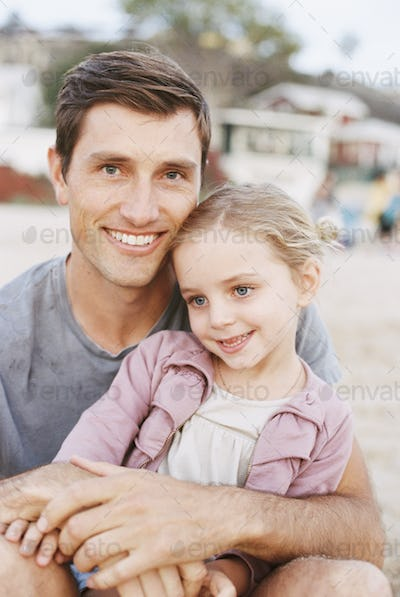 Young girl sitting on her father's lap, looking at camera, smiling.