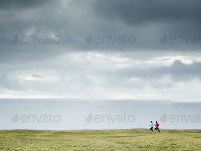 Two women jogging along the coast.
