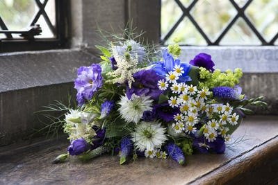 Close up of a bouquet of blue and white wedding flowers.