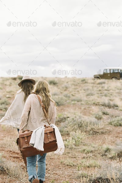 Two women walking towards a 4x4 parked