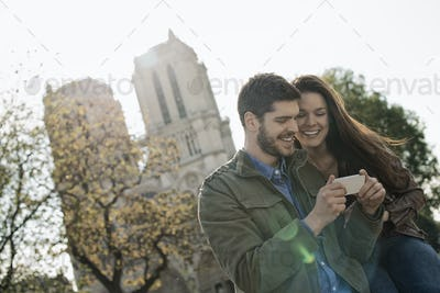 A couple in a historic city, looking at a smart phone.