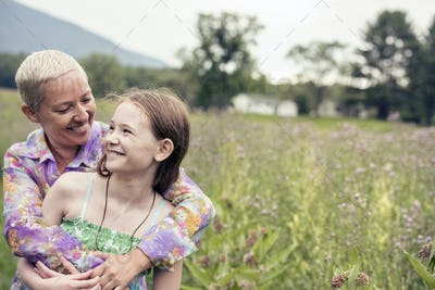 A mature woman and a young girl in a wildflower meadow.