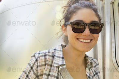 A young woman wearing sunglasses by a silver coloured trailer.