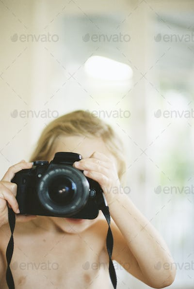 Young nude girl taking a picture with a camera.