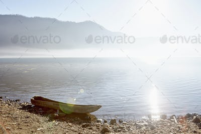 Sunlight on the water of a mountain lake, and a dug out canoe on the shore.