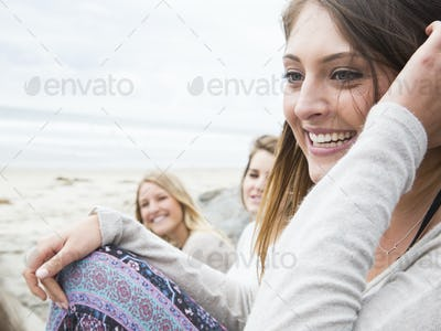 Three smiling young women sitting on a beach.