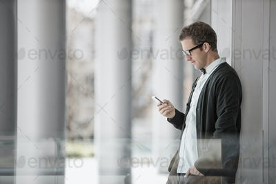 A man in casual clothes standing outside a building, checking his smart phone.