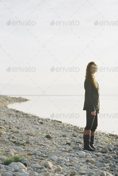 A woman standing on the shore of a lake.