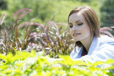A young woman in a garden examining growing plants.