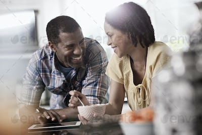 A man and woman, couple in ther kitchen both looking at a digital tablet.