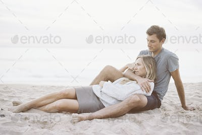 A couple sitting on a beach, a man and woman with their arms around each other.