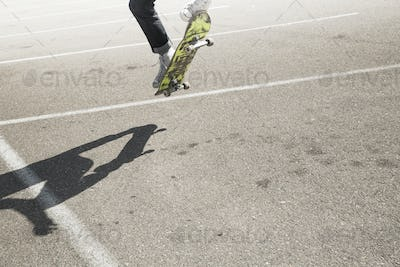 Young man skateboarding in a car park.